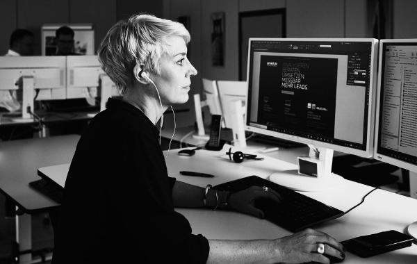 arvenio Mitarbeiterin Patricia Deuring sitzt vor zwei Bildschirmen mit Grafikprogramm geöffnet