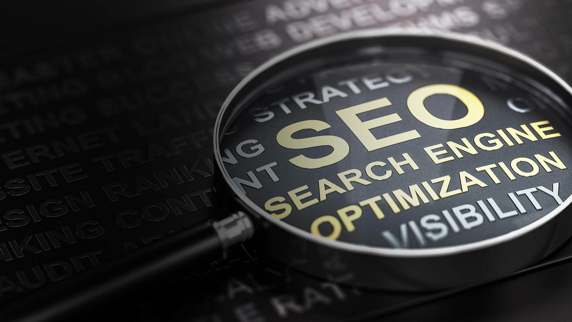 Eine Lupe über einem schwarzen Papier mit Aufschrift SEO Search Engine Optimization