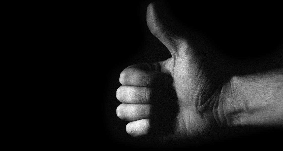 Eine Hand, die den Daumen nach oben streckt auf schwarzem Hintergrund
