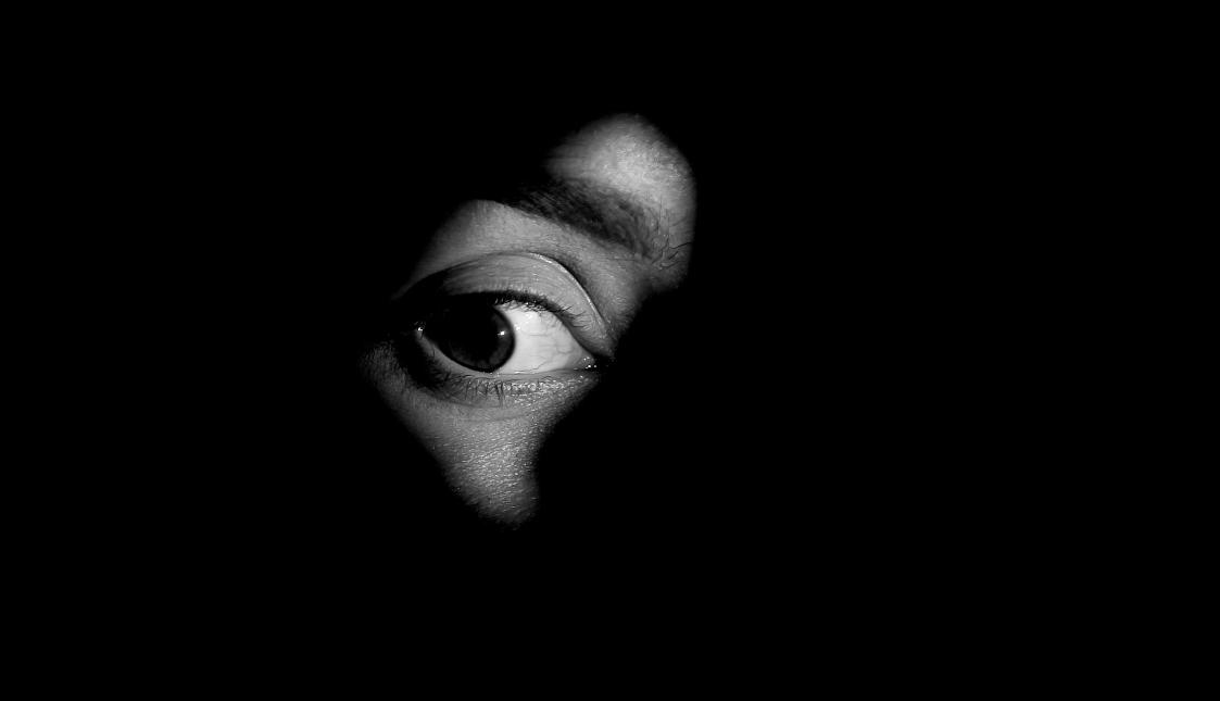 Ein weit offenes Auge in Graustufen und auf schwarzem Hintergrund