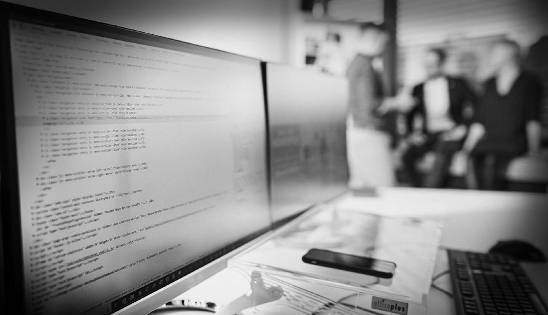 Ein Bildschirm mit Code-Text in einem unscharfen Büro