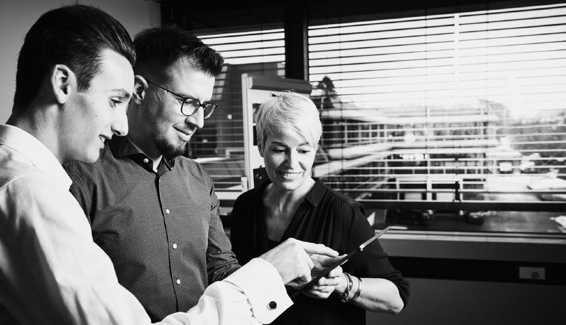 Drei arvenio Mitarbeiter blicken in ein iPad und besprechen sich