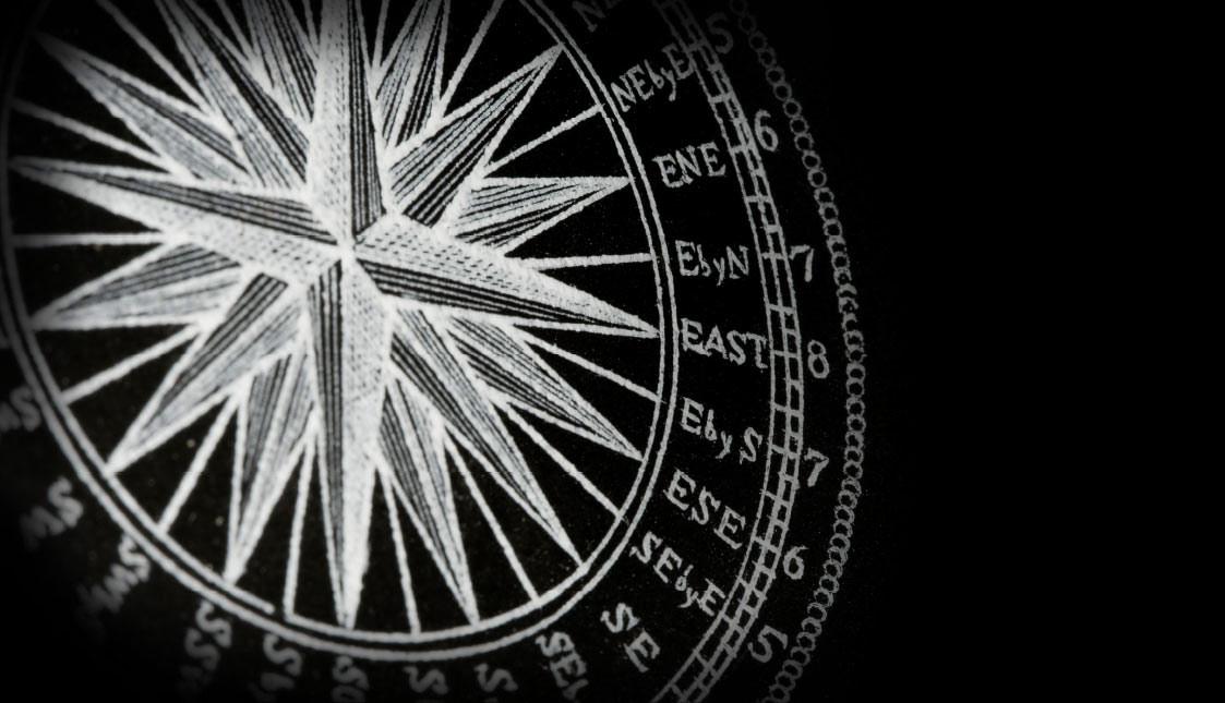 Ein alter weißer Kompass auf schwarzem Hintergrund