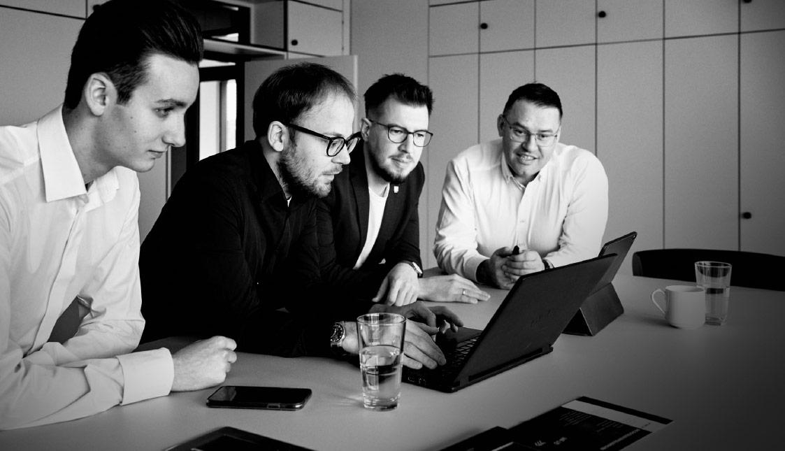 4 arvenio Mitarbeiter vor einem Laptop besprechen ein aktuelles Kundenprojekt