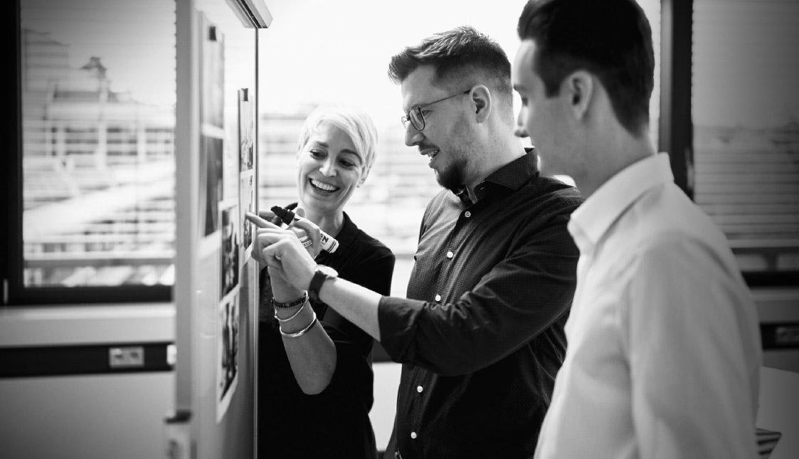 Drei arvenio Mitarbeiter vor einem Flipchart bewerten Fotos