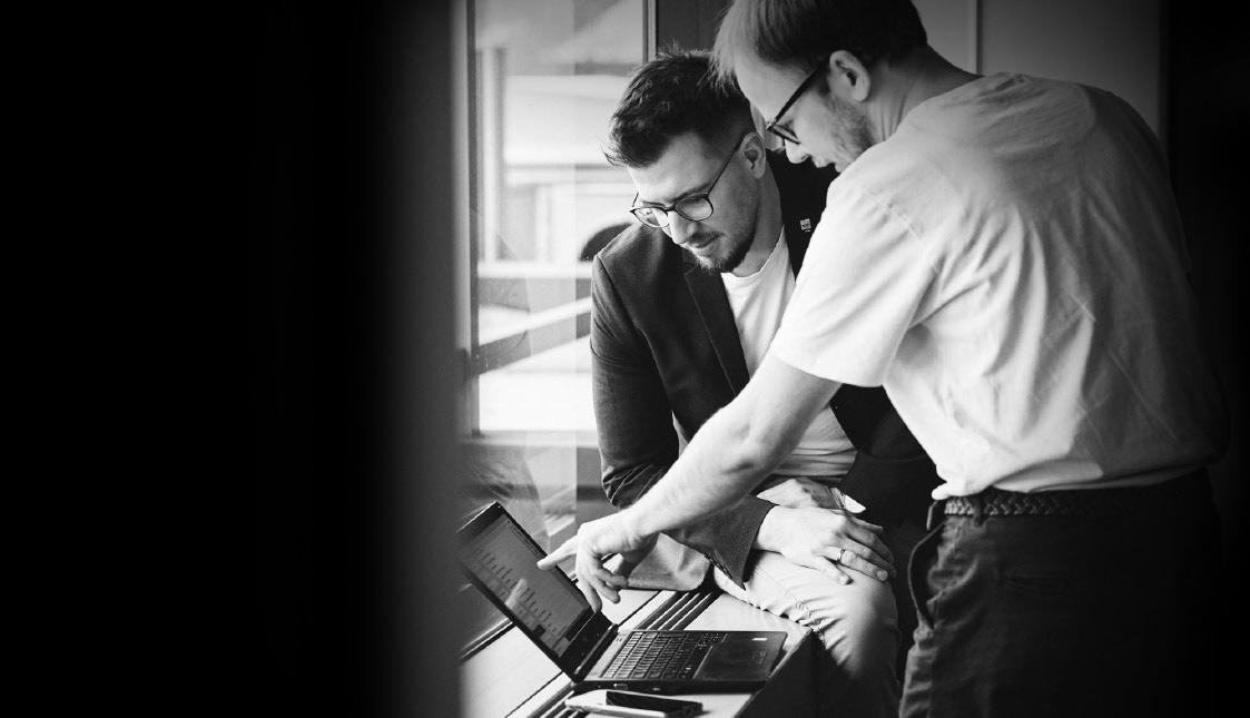 Zwei Mitarbeiter sitzend und stehend mit BLick auf einen Laptop