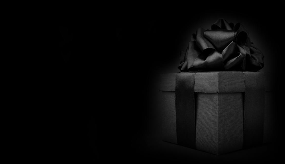 Ein schwarz verpacktes Geschenk vor dunklem Hintergrund