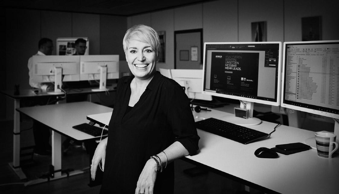 Eine lächelnde Mitarbeiterin in einem Büro vor zwei Bildschirmen