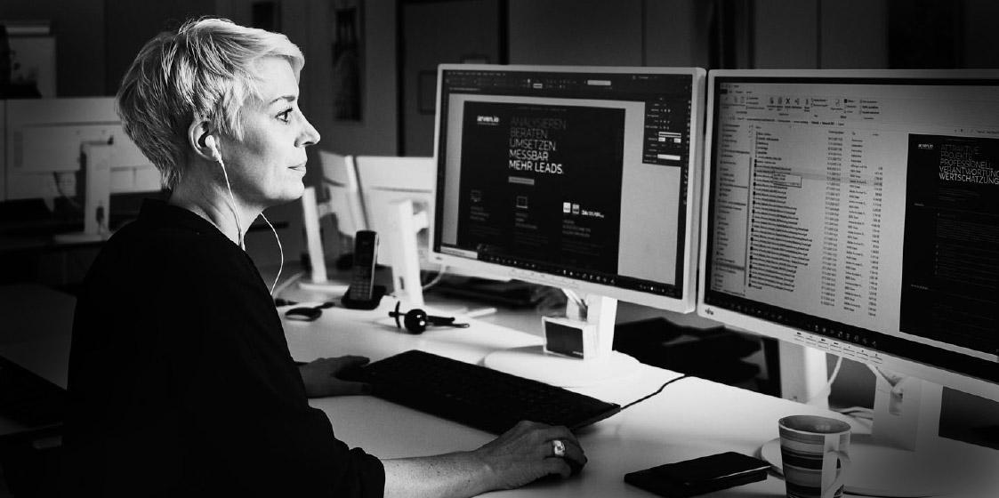 Eine arvenio Mitarbeiterin vor zwei Bildschirmen mit Ohrstöpseln im Ohr