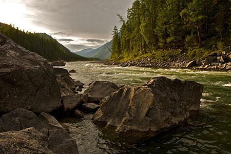 Ein Tal mit Bäumen durch das ein Fluss fliest und Felsen zu sehen sind