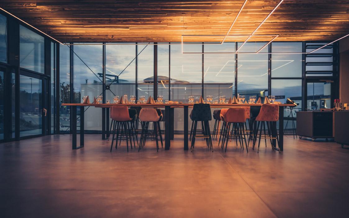 Ein gedeckter Tisch mit bunten Stühlen vor einer Glaswand