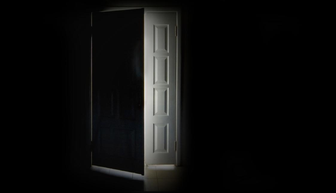 Eine weiße Türe in einem schwarzen Raum