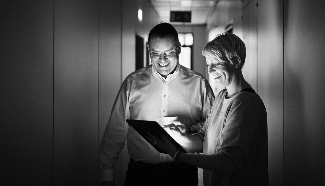 arvenio Geschäftsführer Stefan Walliser und Patricia Deuring im Gespräch über ein Projekt mit Blick auf ein Tablet-PC