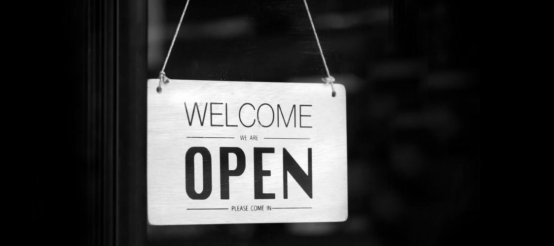 Ein Öffnungsschild eines Ladens in schwarz und weiß