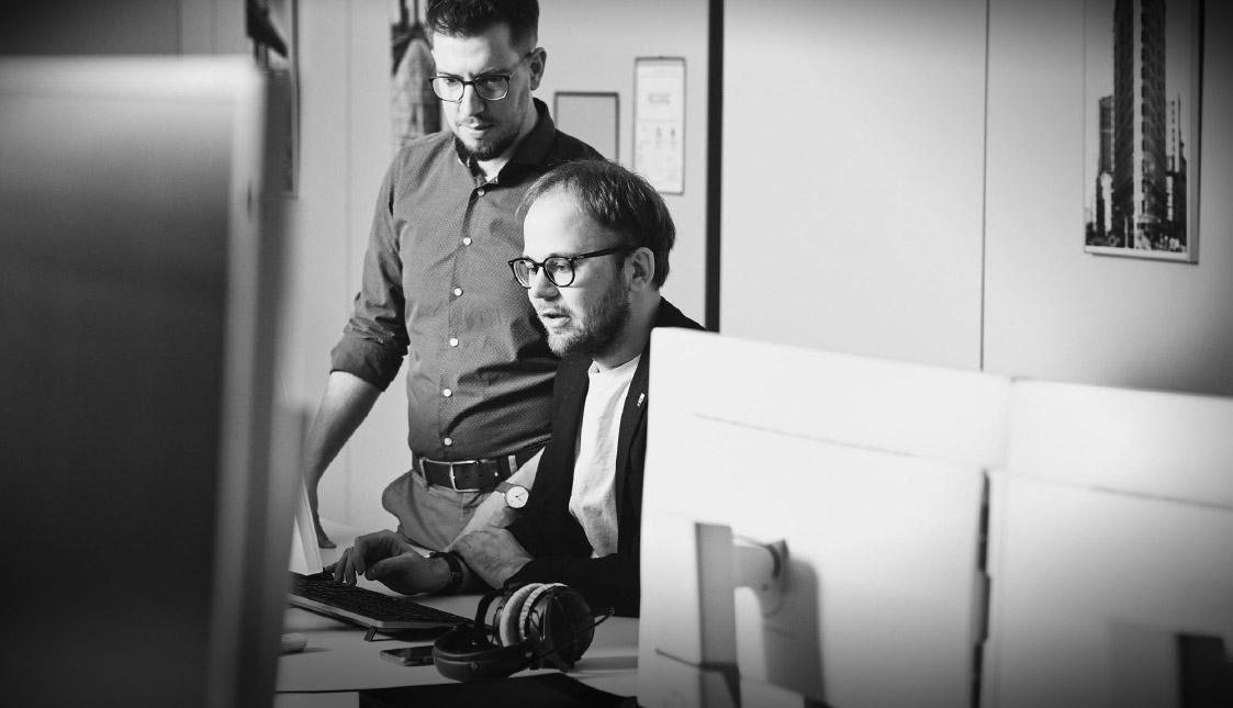arvenio Mitarbeiter Dominik Wubs und Raphael Roth sitzen an einem Schreibtisch und besprechen ein Shop-Projekt