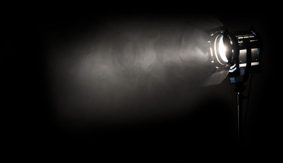 Ein Theaterscheinwerfer mit Nebel vor einem schwarzen Hintergrund