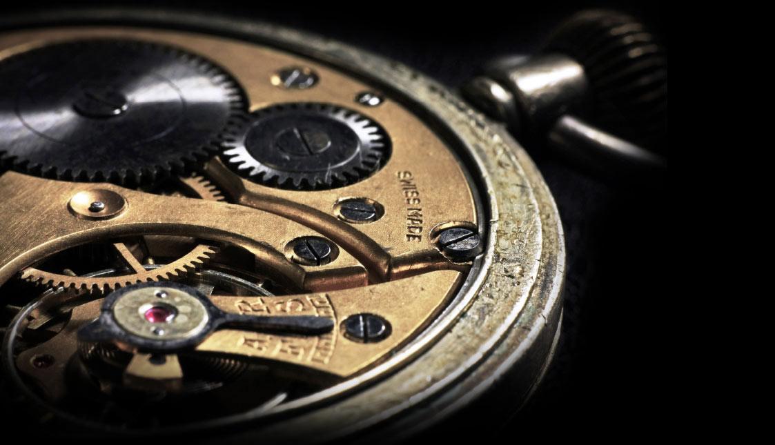 Ein goldenes Uhrwerk auf schwarzem Hintergrund