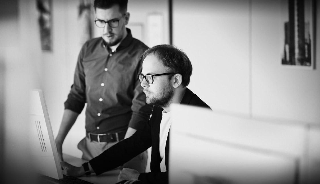 arvenio Mitarbeiter Dominik Wubs und Raphael Roth analysieren einen Kunden vor einem Bildschirm