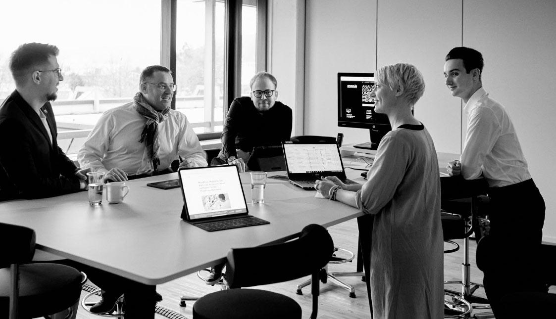 Das arvenio Team bespricht eine strategische Analyse eines Kunden an einem Stehtisch